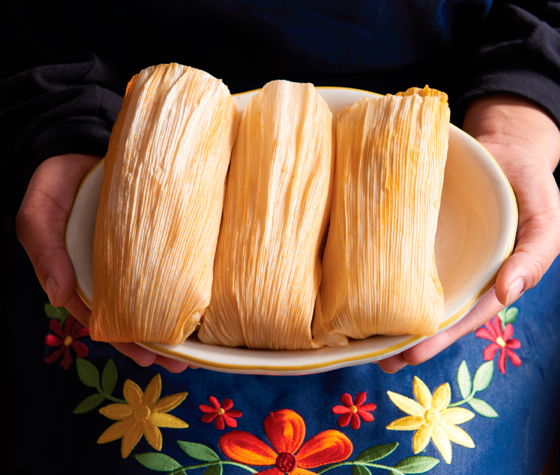 Food photography with hands holding plate of tamales for Alicia's Tamales Los Mayas