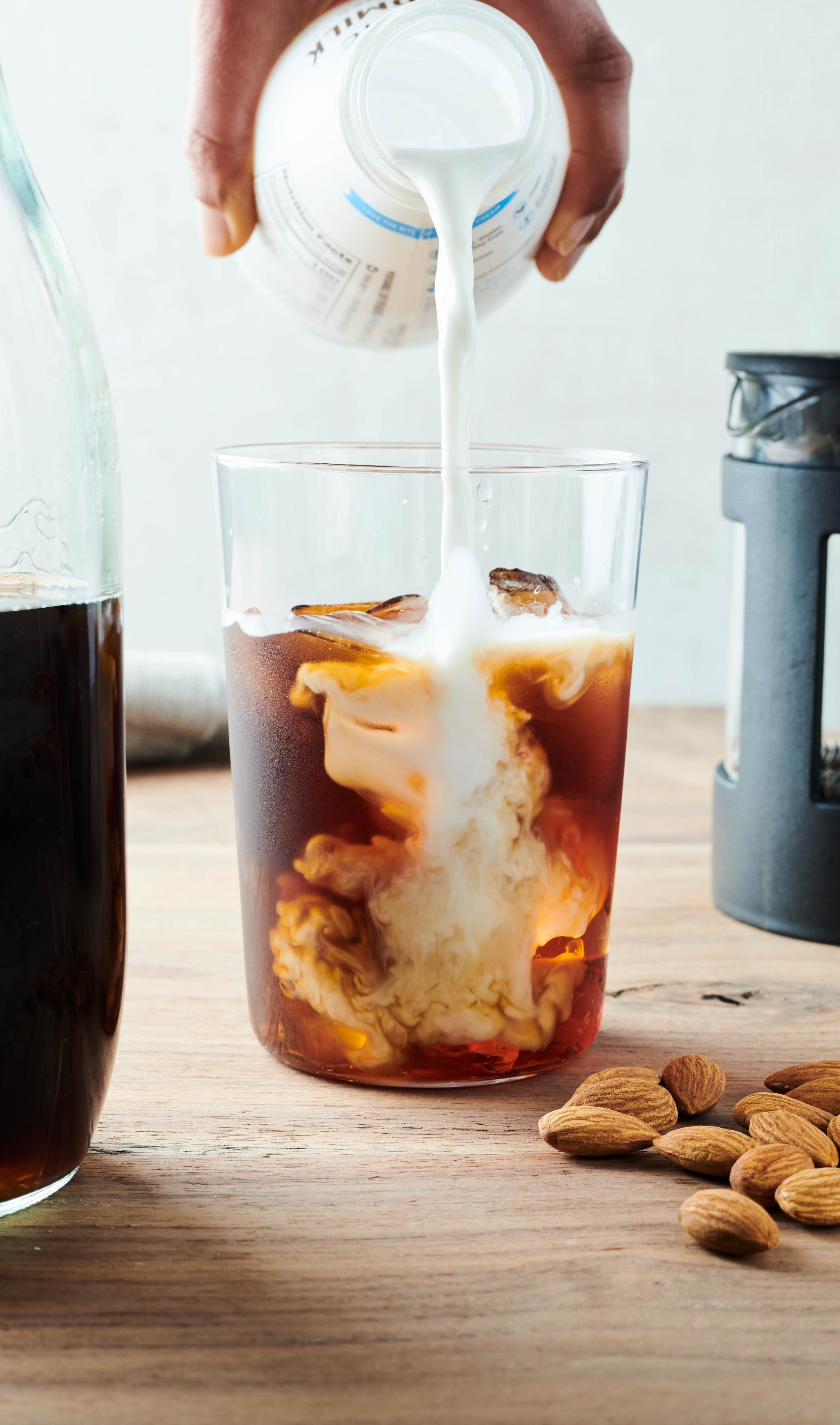 Food Photography with almond pouring into cold brew for Three Trees Almond Milk