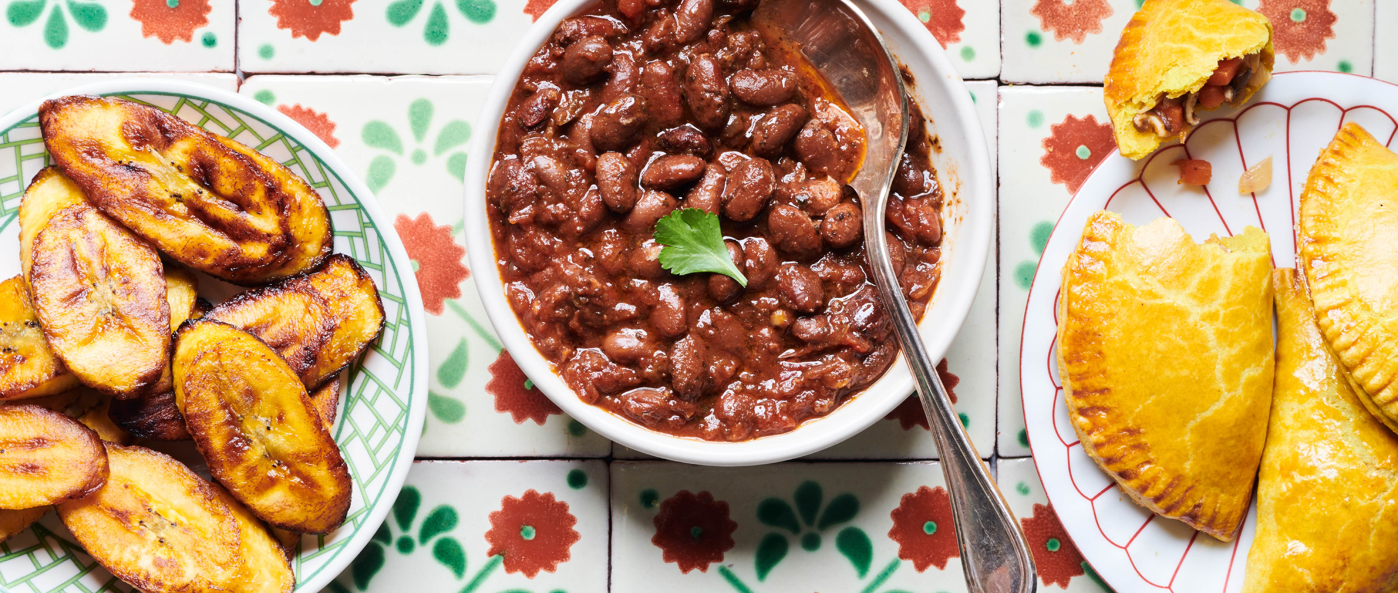 Food photography of a table spread of Caribbean dishes featuing the Cuban Black Beans for A Dozen cousins' Brand